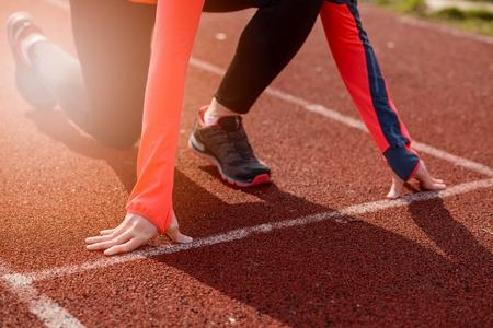 Femme courir la formation à l'extérieur. Jeune femme faisant des exercices et prêt à commencer à courir. Santé et concept de sport.