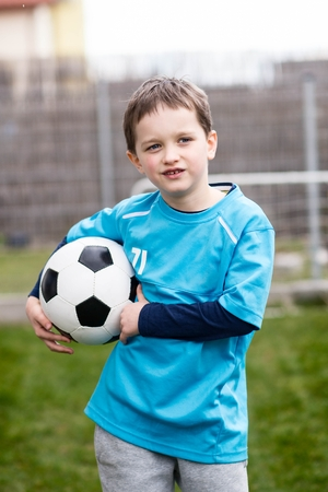 footballer: Portrait of little 7 years boy - footballer with football ball. Child playing football in garden. Wears a blue t-shirt, black and blue shoes and grey sweatpants.