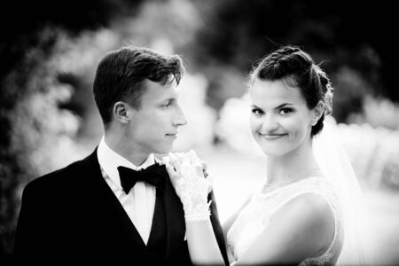 photography session: Bride with hands on the shoulder of the groom. Looking at camera. Black and white photography. Wedding session in the park