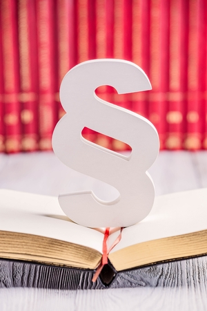 legality: White wooden paragraph the symbol of law in court library with legal codes. Law concept Stock Photo
