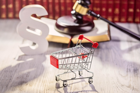 commercial law: Little trolley - pushcart with the symbols of law in court library with legal codes. Commercial law concept