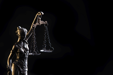 Statuette of the goddess of justice Themis with scales - isolated on black background. Law concept Stockfoto