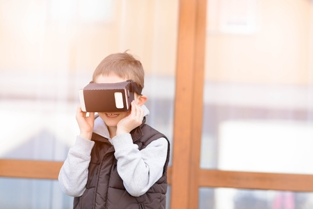 google play: Fascinated little boy using VR virtual reality goggles- outdoor Stock Photo
