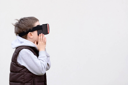 google play: Fascinated little boy using VR virtual reality goggles- white background