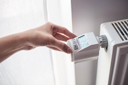 女性の手の家の壁のヒーターの温度を調整します。