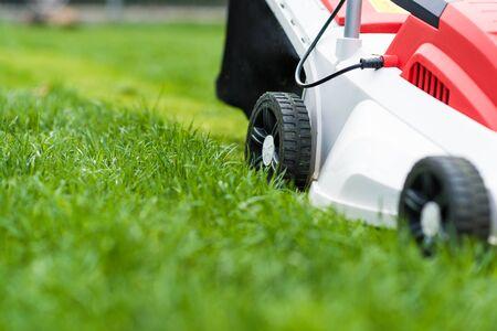 Lawn mower cutting green grass. Work in the garden. Spring gardening Stock Photo