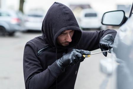ladron: El hombre vestido de negro con una capucha en la cabeza tratando de entrar en el coche. ladrón de coches, el concepto de robo de automóviles Foto de archivo