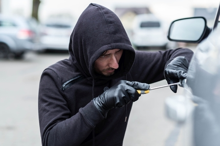 breakin: The man dressed in black with a hood on his head trying to break into the car.  Car thief, car theft concept Stock Photo