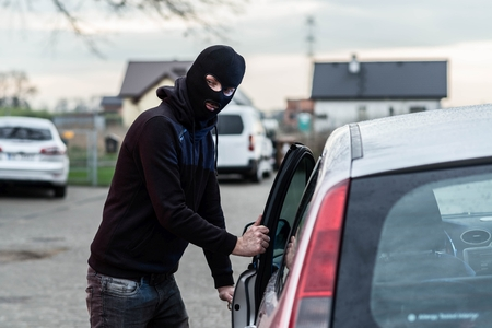 robo de autos: Man dressed in black with a balaclava on his head entering the vehicle and stealing a car. Car thief, car theft concept Foto de archivo