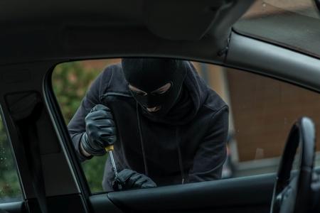 robo de autos: El hombre vestido de negro con un pasamontañas en la cabeza tratando de entrar en el coche. Utiliza un destornillador. ladrón de coches, el concepto de robo de automóviles Foto de archivo