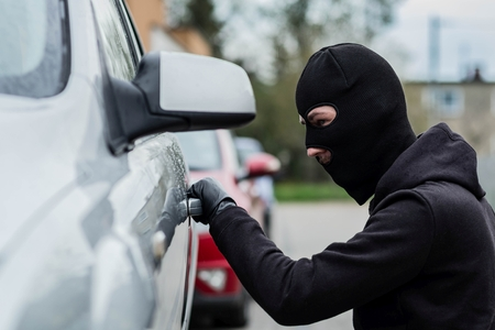 robo de autos: Hombre vestido de negro con un pasamontañas en la cabeza tira de la manija de un coche. ladrón de coches, el concepto de robo de automóviles Foto de archivo