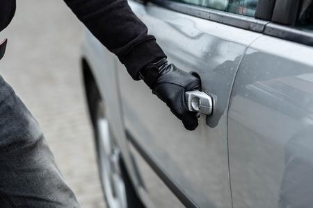 車のハンドルを引く車泥棒の手にクローズ アップ。車泥棒は、車の盗難のコンセプト