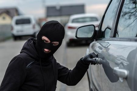 robo de autos: Man dressed in black with a balaclava on his head pulls the handle of a car. Car thief, car theft concept