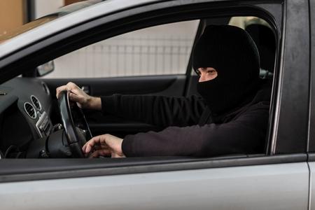 robo de autos: El hombre vestido de negro, con un pasamontañas en la cabeza conducir un coche robado. ladrón de coches, el concepto de robo de automóviles