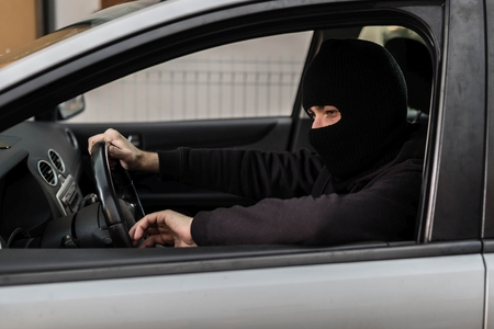 car theft: Man dressed in black with a balaclava on his head driving a stolen car. Car thief, car theft concept