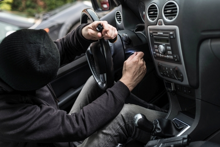 Man dressed in black with a balaclava on his head trying to run a car. Car thief, car theft concept Reklamní fotografie