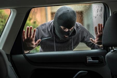 robo de autos: Hombre vestido de negro con un pasamontañas en la cabeza mirando a través de la ventana del coche y se preguntaba cómo introducirse en este coche. ladrón de coches, el concepto de robo de automóviles