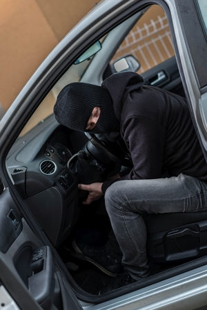 robo de autos: El hombre vestido de negro, con un pasamontañas en la cabeza tratando de ejecutar un coche. ladrón de coches, el concepto de robo de automóviles
