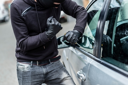 disarm: The man dressed in black with a balaclava on his head trying to break into the car. He uses a screwdriver. Car thief, car theft concept Stock Photo