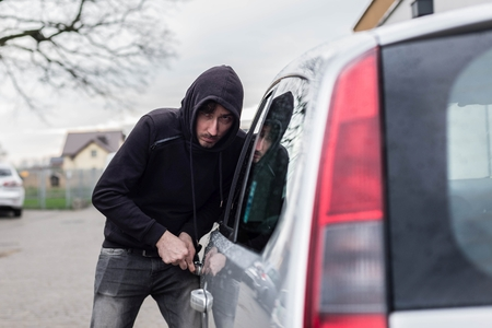 car theft: The man dressed in black with a hood on his head trying to break into the car.  Car thief, car theft concept Foto de archivo