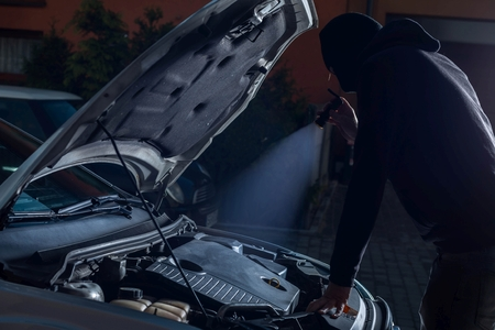 car theft: Car thief with flashlight disarming car protections against theft. Car thief, car theft concept