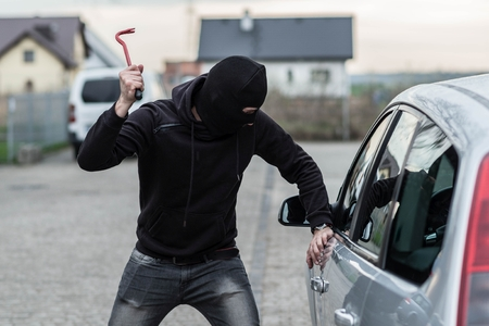 looter: Man dressed in black with a balaclava on his head breaking a glass in car with crowbar. Car thief, car theft concept