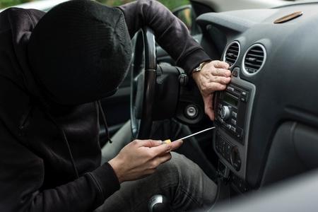 car theft: Hombre vestido de negro con un pasamonta�as en la cabeza tratando de robar la radio de coche con un destornillador. ladr�n de coches, el concepto de robo de autom�viles Foto de archivo