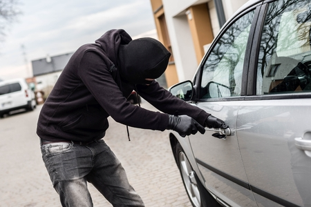 car theft: The man dressed in black with a balaclava on his head trying to break into the car. He uses a screwdriver. Car thief, car theft concept Foto de archivo