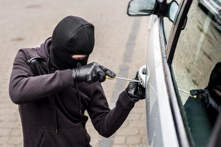 ladron: El hombre vestido de negro con un pasamontañas en la cabeza tratando de entrar en el coche. Utiliza un destornillador. ladrón de coches, el concepto de robo de automóviles Foto de archivo