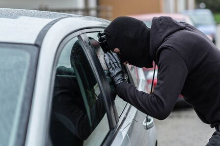 car theft: Man dressed in black with a balaclava on his head looking through car window and wondering how to break into this car. Car thief, car theft concept Foto de archivo