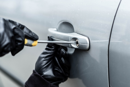 Close up on car thief hands trying to steal a vehicle with screwdriver Foto de archivo