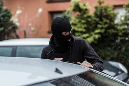 disarm: Man dressed in black with a balaclava on his head entering the vehicle and stealing a car. Car thief, car theft concept Stock Photo