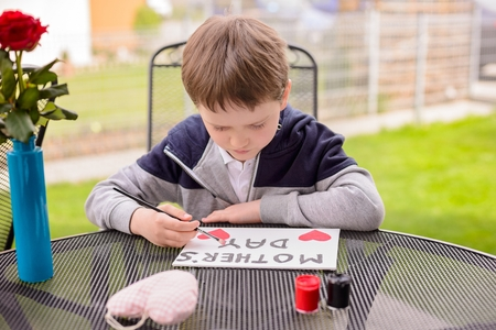 7 year old: Little 7 year old boy paints greeting card for Mom on Mothers Day with the inscription Mothers Day. Outdoors. Mothers Day