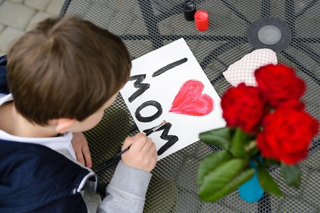 7 year old: Little 7 year old boy paints greeting card for Mom on Mothers Day with the inscription I love you mom. Outdoors. Mothers Day