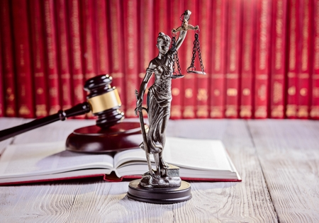 Symbols of law in court  library. Judge gavel, goddess of justice Themis and legal codes. Law concept Stockfoto