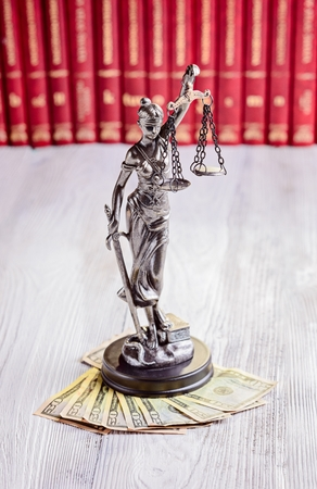 themis: Statuette of Themis and american dollars in court library. Bribe and law concept