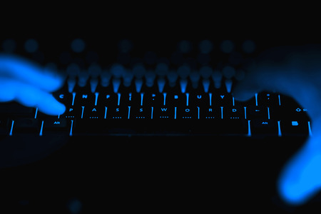 spy: Hacker hands typing on the illuminated buttons of the keyboard by night. Internet safety concept.