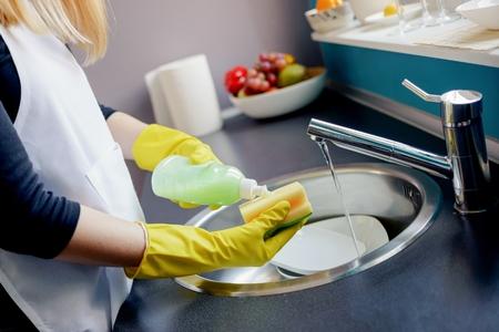 Vrouw in gele beschermende rubberen handschoenen afwassen in de keuken met spons.