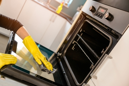 Closeup on woman's hands in yellow protective rubber gloves cleaning oven with rag Standard-Bild