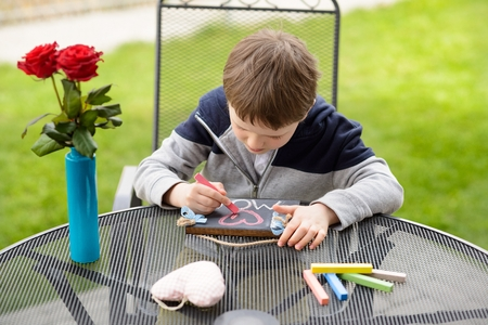 love declaration: Little boy child drawing a love declaration on small blackboard for his mother on Mothers Day. Stock Photo