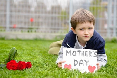 selfmade: Mothers Day - Boy giving his mother self-made greeting card and flowers - red roses.