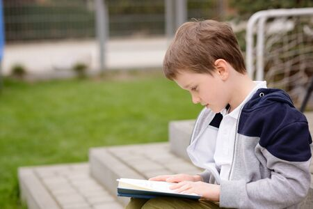 7 year old: 7 year old boy, a student reading a book on the terrace in the garden