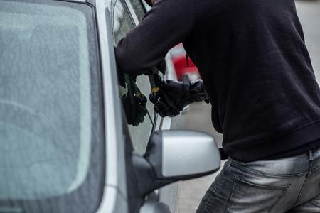 robo de autos: Car thief trying to break into a car with a screwdriver. Car thief, car theft.
