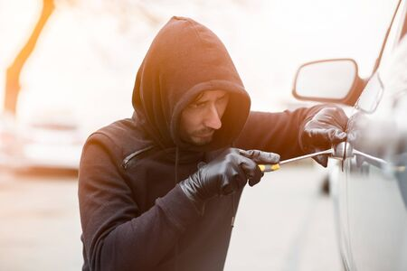 breakin: Car thief trying to break into a car with a screwdriver. Car thief, car theft.