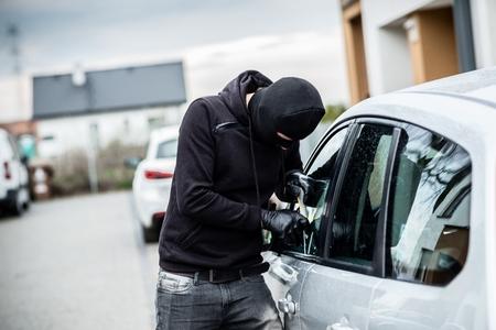 robo de autos: ladrón de coches que intenta penetrar en un coche con un destornillador. ladrón de coches, el robo de vehículos.