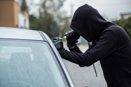 car theft: ladr�n de coches que intenta penetrar en un coche con un destornillador. ladr�n de coches, el robo de veh�culos.