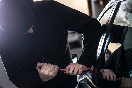 Car Thief tries to break into car with crowbar. Car thief, car theft Stock Photo