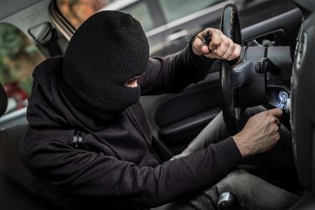 robo de autos: Ladrón de coches intenta arrancar el coche con un destornillador en el encendido. ladrón de coches, el robo de automóviles Foto de archivo