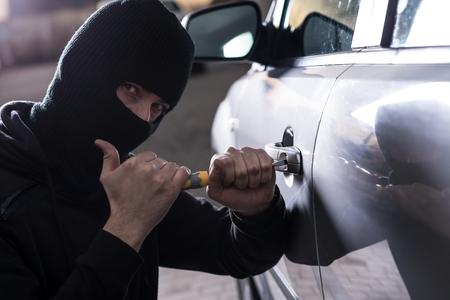 robo de autos: Ladrón de coches intenta abrir un coche con un destornillador. ladrón de coches, el robo de automóviles