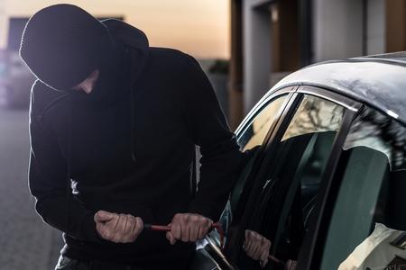 Car Thief tries to break into car with crowbar. Car thief, car theft